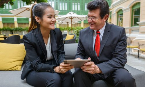 Happy mature businessman and young Asian businesswoman using digital tablet together